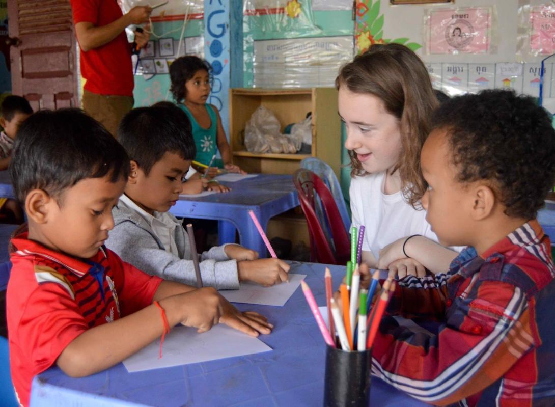 Una voluntaria ayudando niños en un centro de atención comunitaria en vez de un orfanato en Camboya.